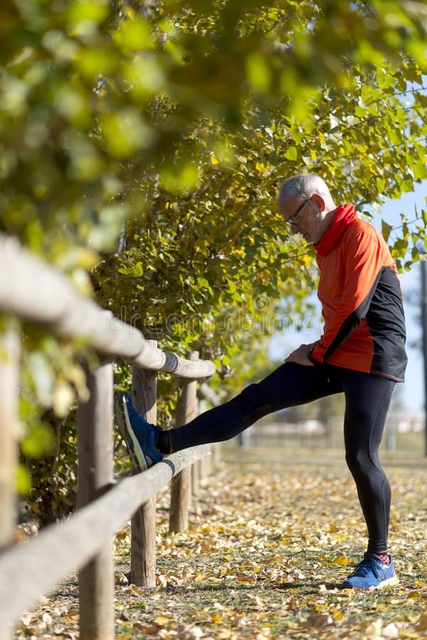 Senior man stretching his leg. Doing workout in nature. Healthy living. Forest. Outdoors stock image