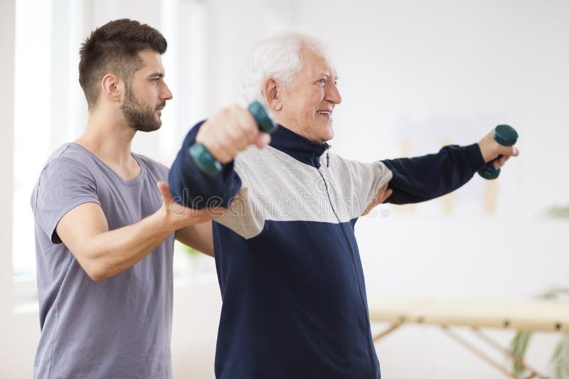 Senior man after stroke at nursing home exercising with professional physiotherapist royalty free stock images
