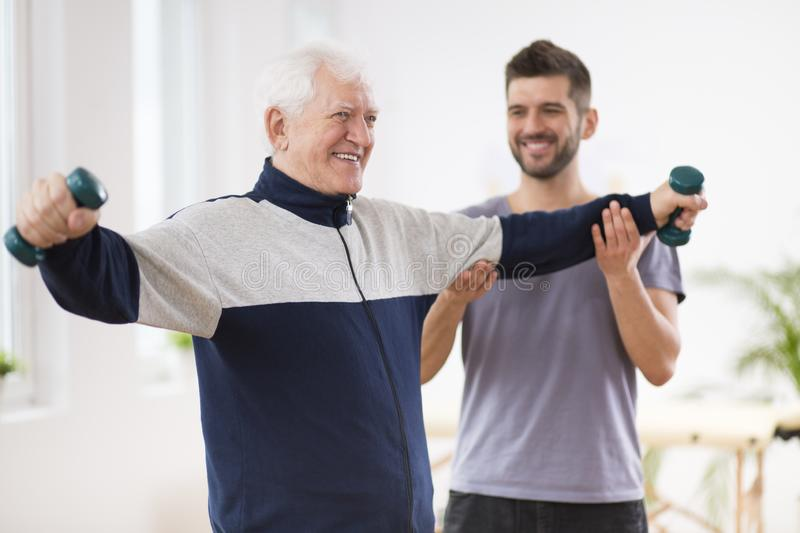 Senior man after stroke at nursing home exercising with professional physiotherapist stock photo