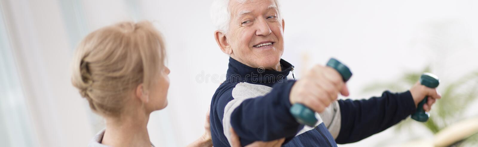 Senior man after stroke at nursing home exercising with professional physiotherapist royalty free stock photography