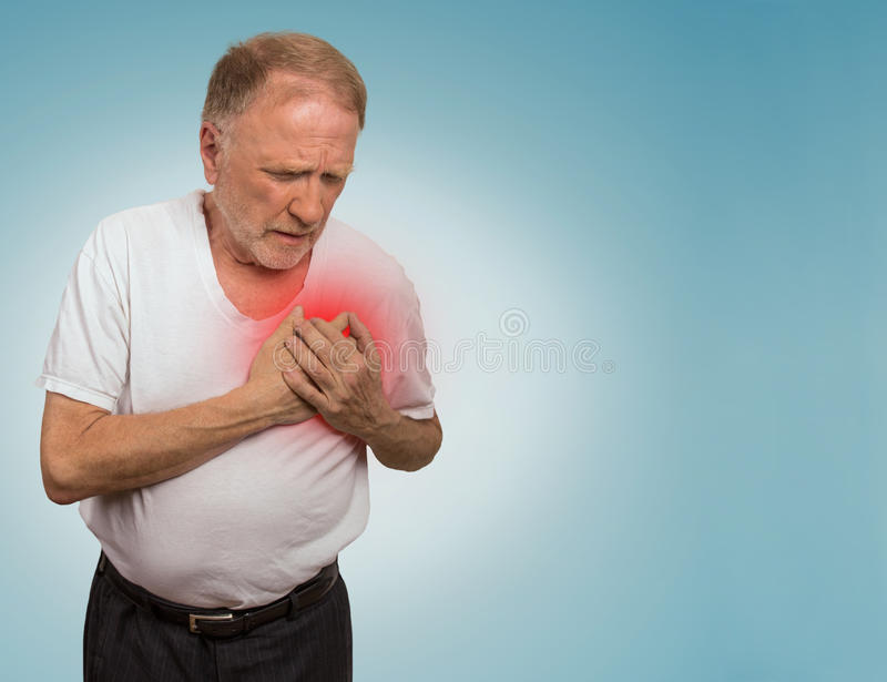 Senior man suffering from bad pain in his chest. Isolated on blue background stock images