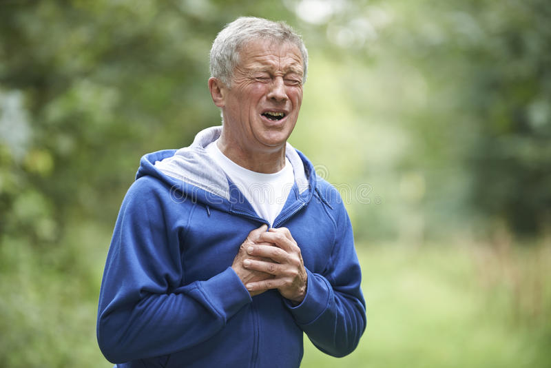 Senior Man Suffering Heart Attack Whilst Jogging stock image