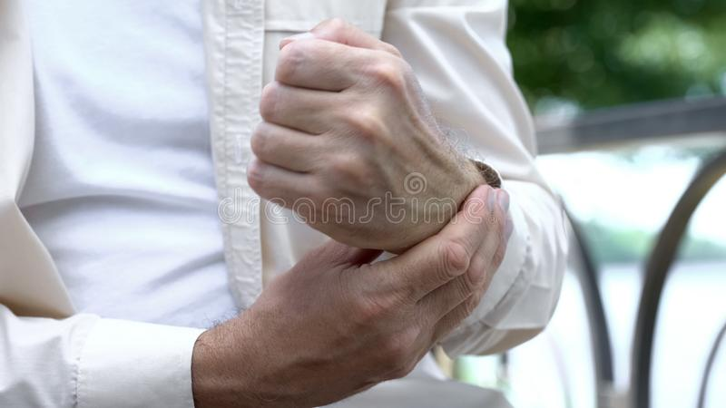 Senior man suffering pain in arm, problem with joint inflammatory arthritis stock photography
