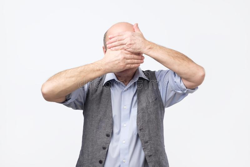 Senior man suffering from painful feelings griefing bending head down covering face with palms royalty free stock images