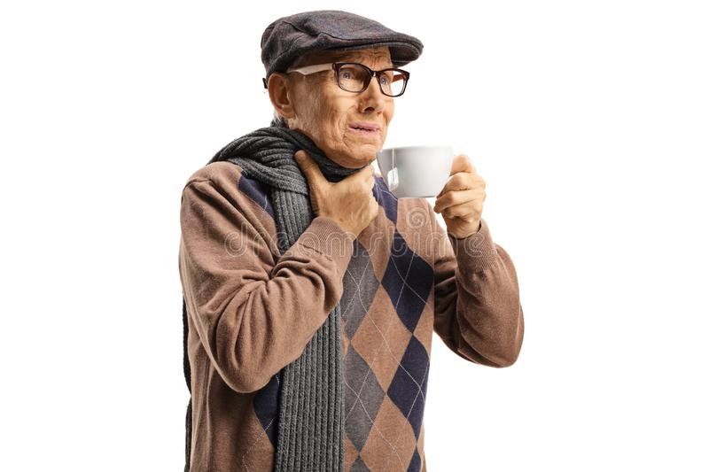 Senior man suffering from sore throat and having a hot tea stock image