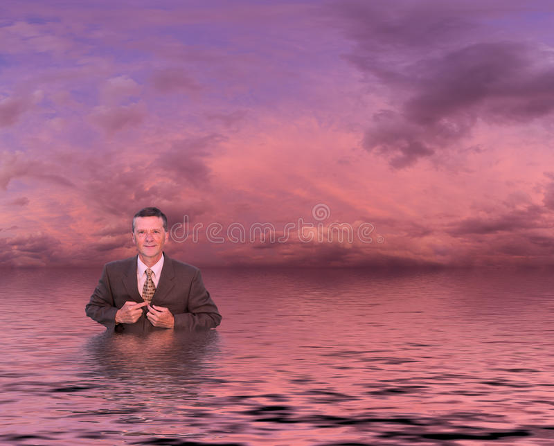 Senior man in suit in deep water. Conceptual image of senior businessman in suit up to waist in deep water. Man is looking proud and confident and the sunset royalty free stock photos