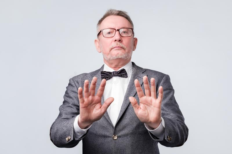 Senior man in suit and glasses showing stop sign against white background royalty free stock images