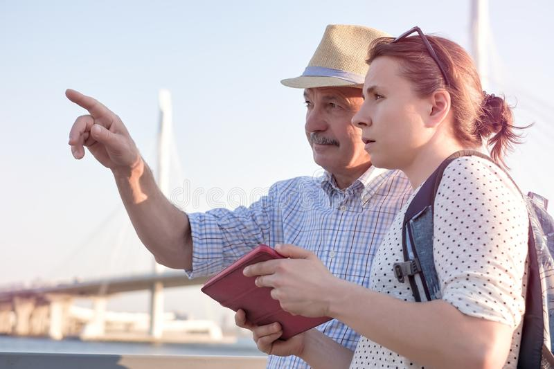 Senior man in summer hat shows the way on the map to young woman. stock image