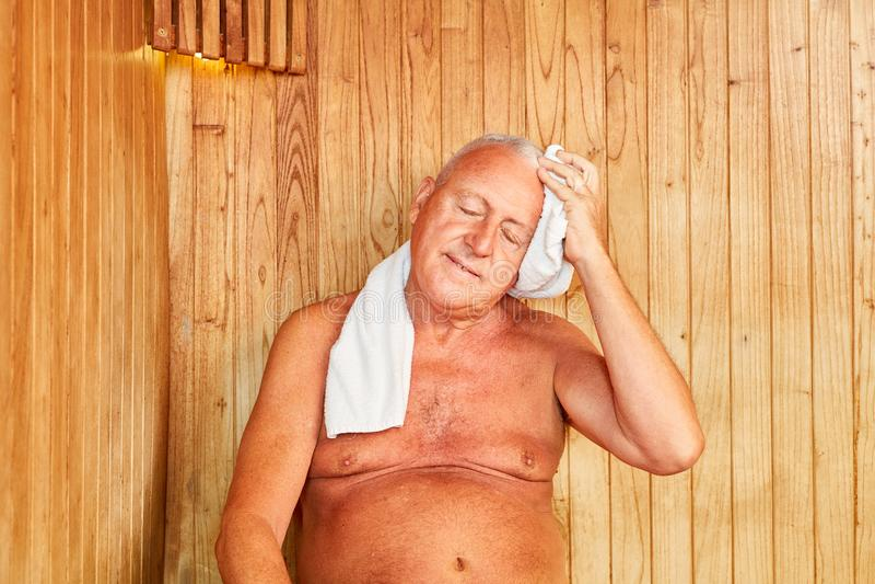 Senior man sweats in the steam sauna royalty free stock photography