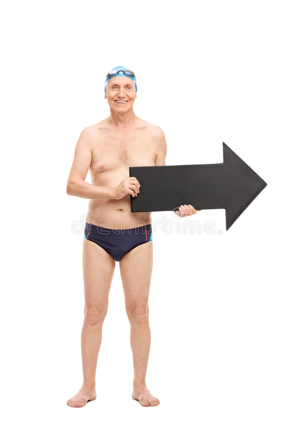 Senior man in a swim trunks holding an arrow. Full length portrait of a senior man in a black swim trunks holding a big black arrow pointing right and looking at stock image