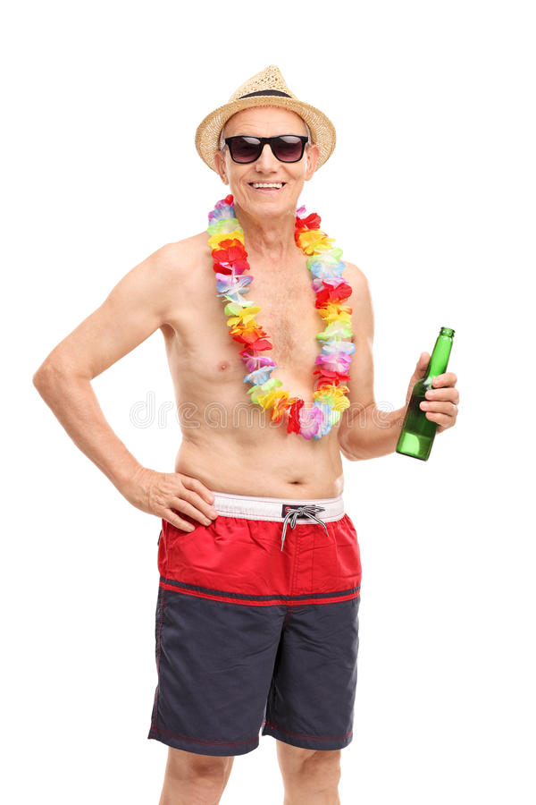 Senior man in a swim trunks holding a beer. Vertical shot of a senior man in a swim trunks holding a beer and looking at the camera isolated on white background stock photography