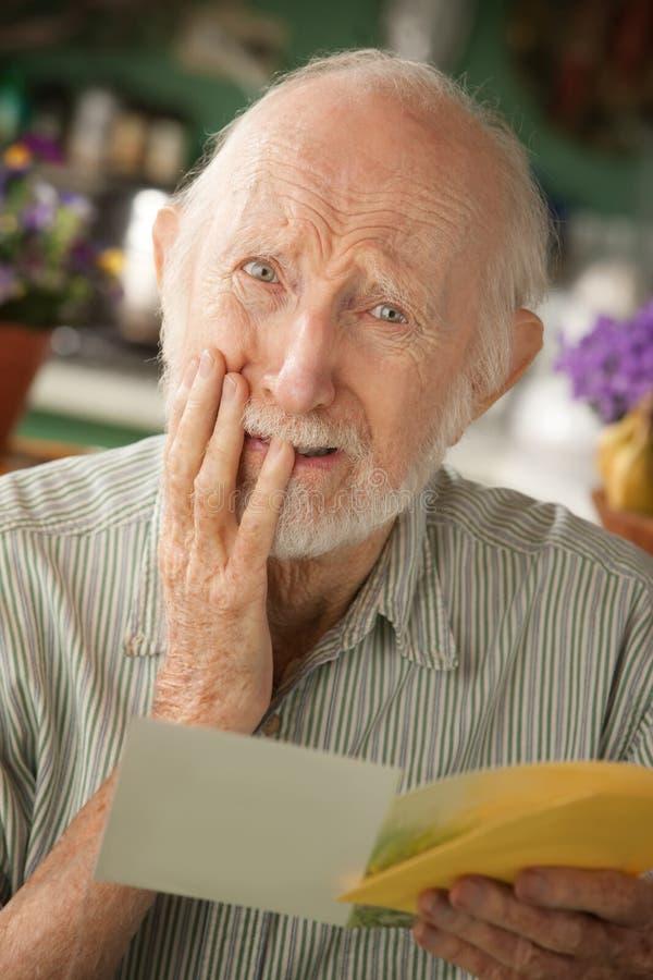 Senior man with sympathy card. Senior man at home reading sympathy card royalty free stock photography