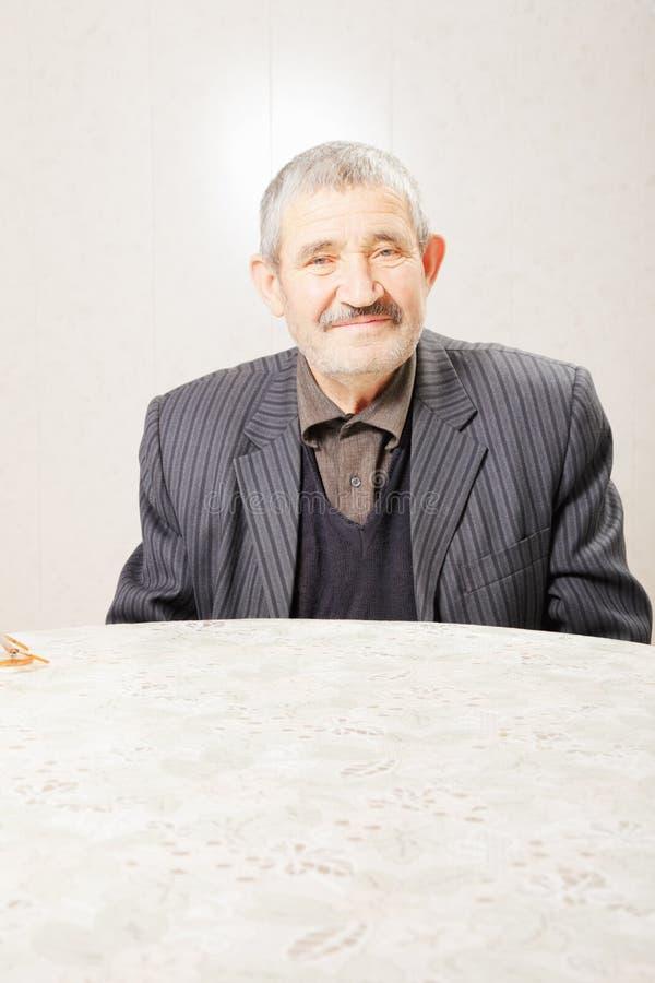 Senior man at table stock photography
