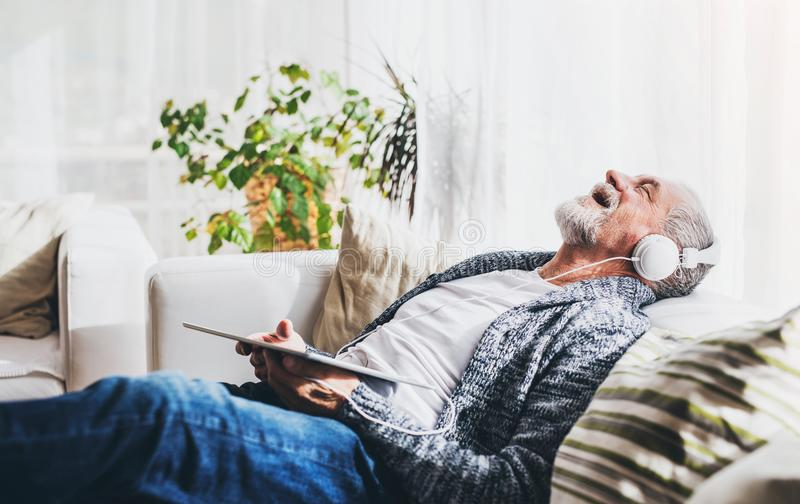 Senior man with tablet relaxing at home. stock image