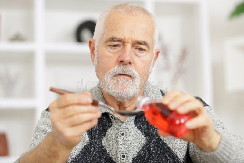 Senior man taking coughing medicin stock images