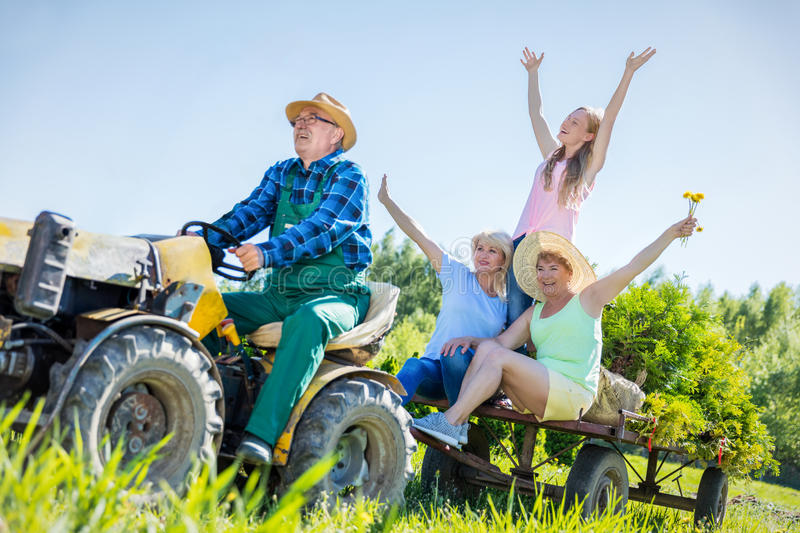 Senior man taking family for ride on tractor. Senior men taking waving family for ride on tractor trailer across countryside field in summer stock image