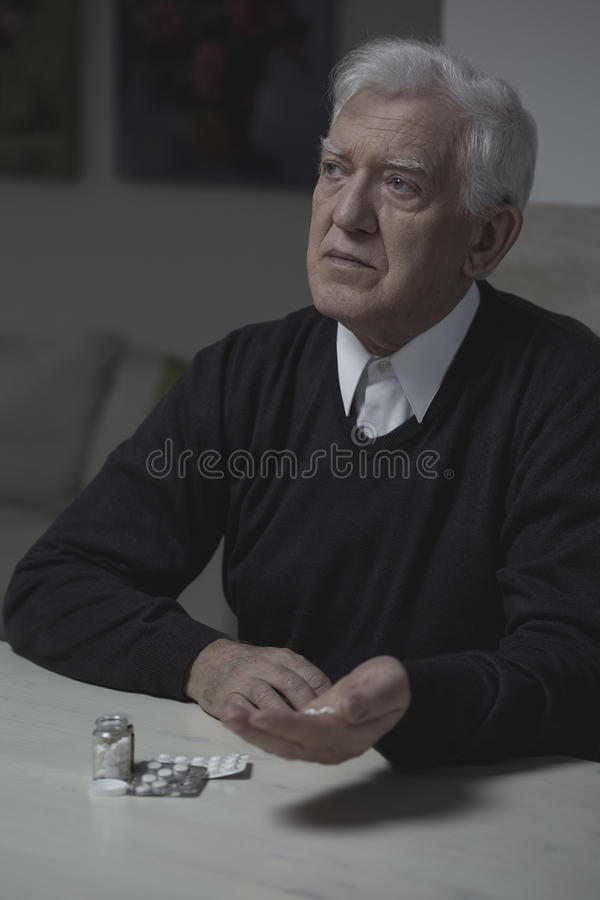 Senior man taking medicament. Senior lonely man taking medicament for depression royalty free stock photos