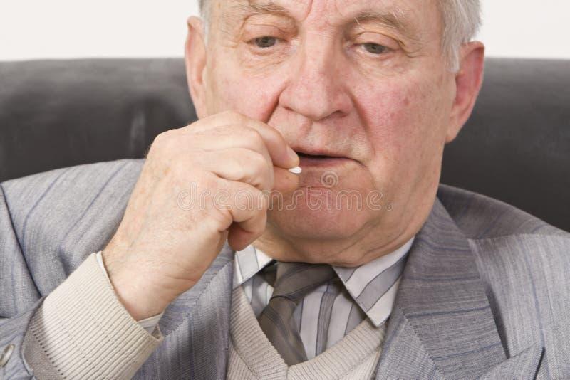 Senior man taking medication royalty free stock image