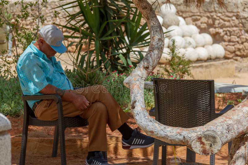 Senior man taking an outside nap in the medieval city of Famagusta on a summer morning stock photos