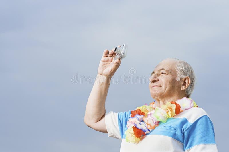 Senior man taking a photograph stock photos