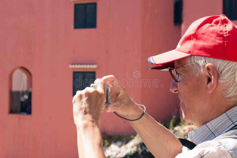 Senior man taking photos with compact camera royalty free stock photos