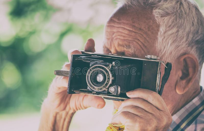 Old man with analog camera. Senior man taking photos with old analog camera in park stock image