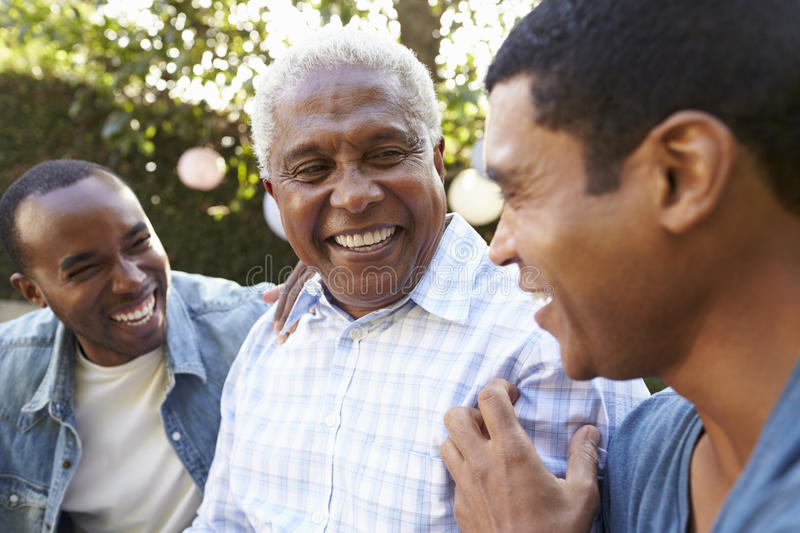 Senior man talking with his adult sons in garden, close up stock image