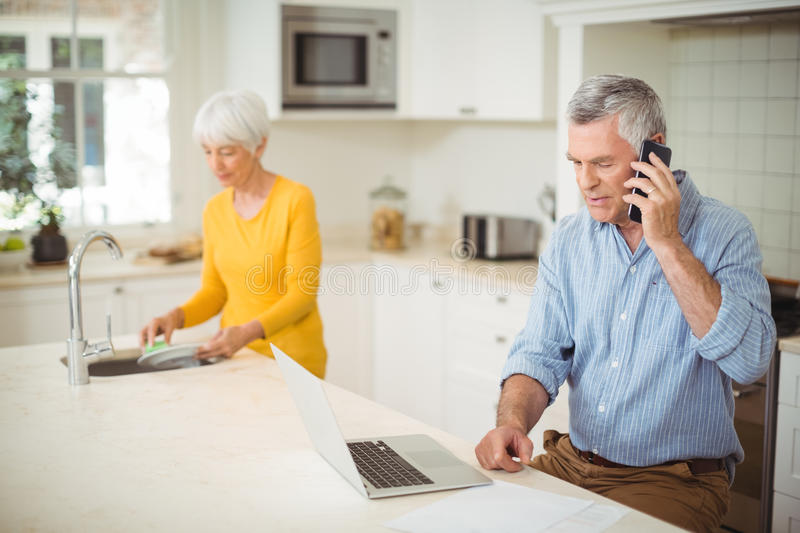 Senior man talking on mobile phone while woman washing plate in kitchen. Senior men talking on mobile phone while women washing dishes in kitchen at home royalty free stock photo