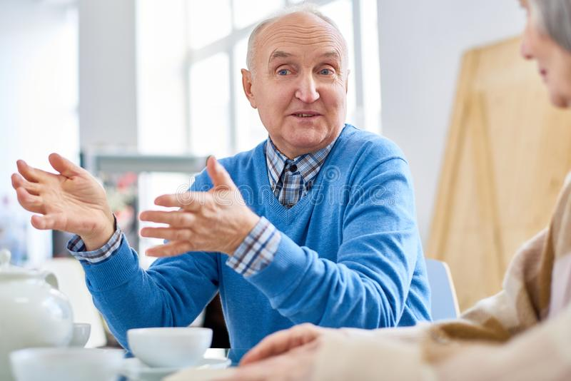 Senior man talking to friends in nursing home stock image