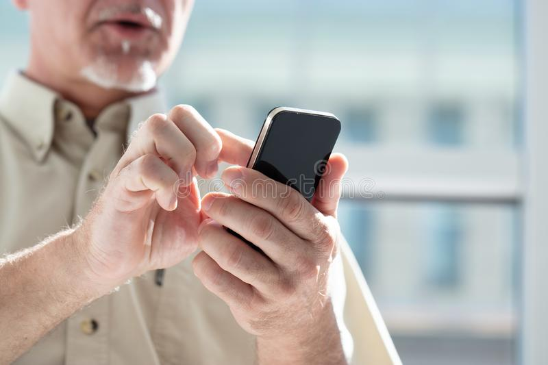Senior man texting a mobile phone message stock photos