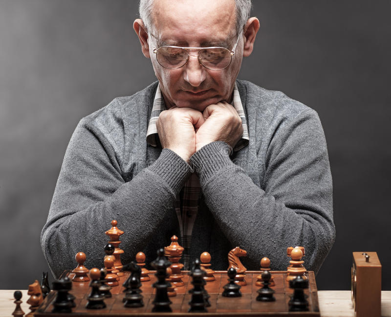 Senior man thinking about his next move in a game of chess. Front view royalty free stock image