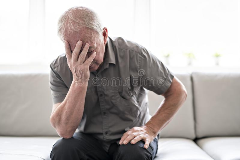 Senior man thinking and sitting on sofa at home like sad royalty free stock photo