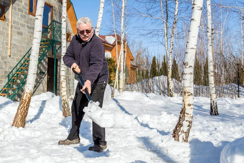 Senior man throwing snow with shovel from private house yard in winter on bright sunny day. Elderly person removing snow in garden stock photos