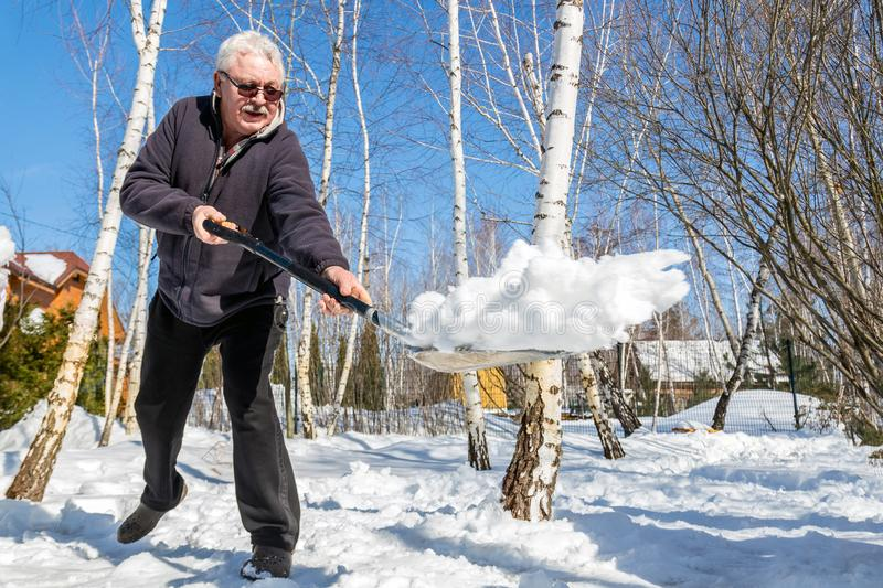 Senior man throwing snow with shovel from private house yard in winter on bright sunny day. Elderly person removing snow in garden royalty free stock photography