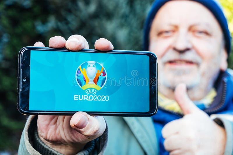 Senior Man tient un smartphone avec le logo de l'UEFA Euro 2020 à l'écran image stock