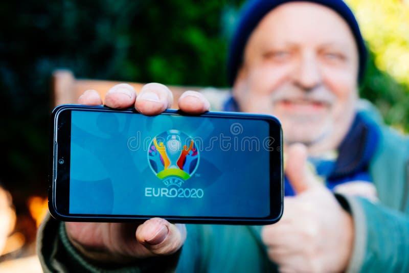 Senior Man tient un smartphone avec le logo de l'UEFA Euro 2020 à l'écran image libre de droits