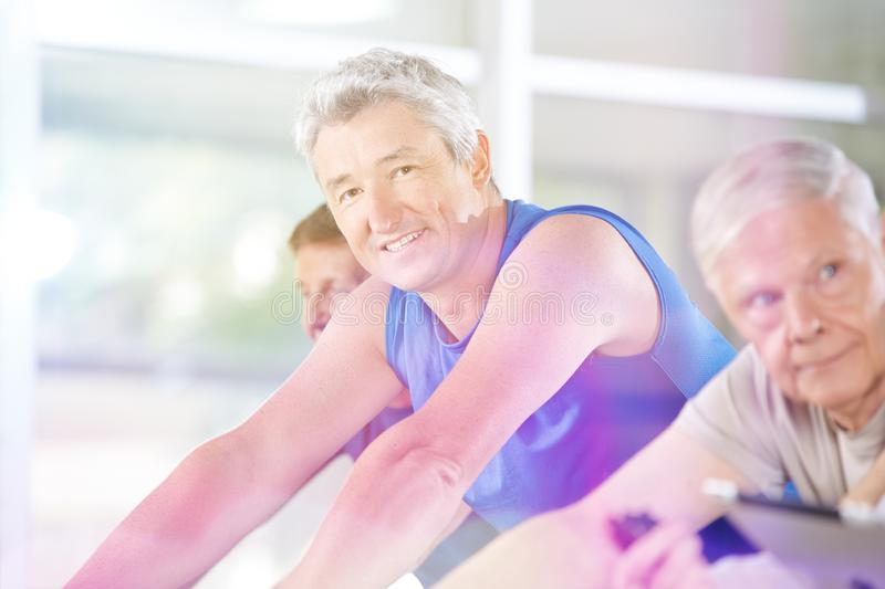 Senior man trains on bicycle in the fitness center royalty free stock photography
