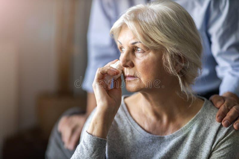 Senior man troostte zijn huilende vrouw royalty-vrije stock afbeeldingen