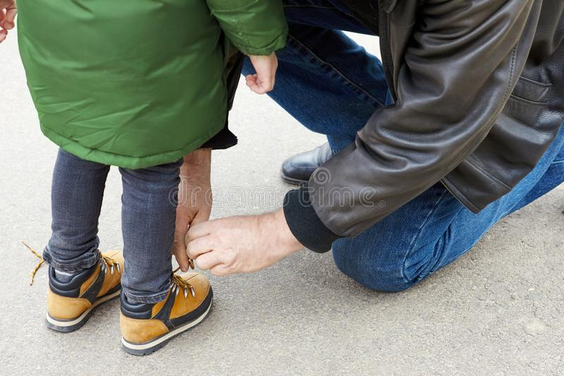 Senior man tying the laces on a child boots. Father or grandfather helps his little son or grandson. The both wearing casual. stock photos