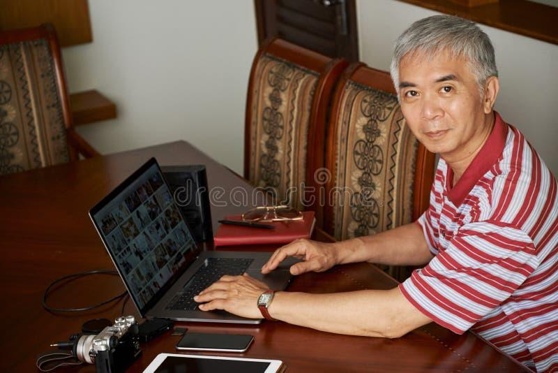 Senior man editing photos on laptop stock photos