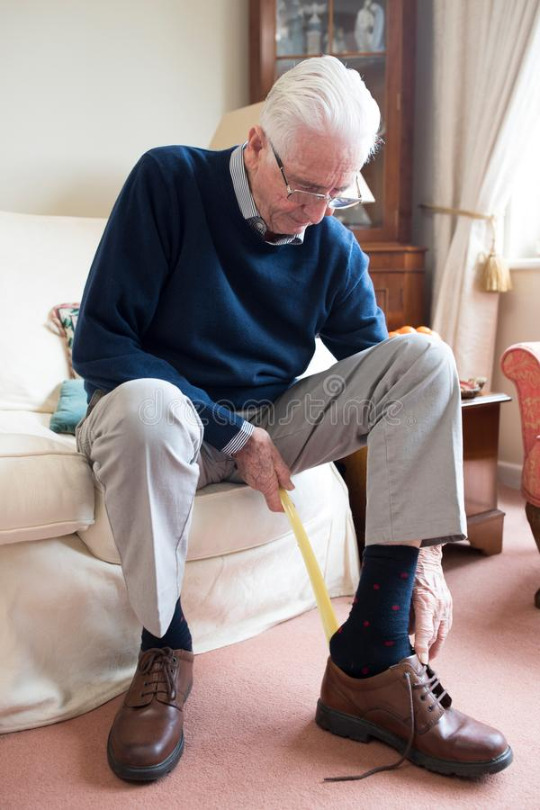 Senior Man Using Long Handled Shoe Horn To Put On Shoes. Senior Man Uses Long Handled Shoe Horn To Put On Shoes stock photo
