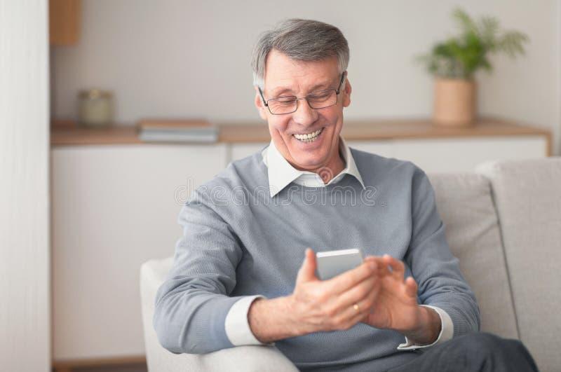 Senior Man Using Cellphone Browsing Internet Sitting Su Sofa Indoor fotografia stock libera da diritti