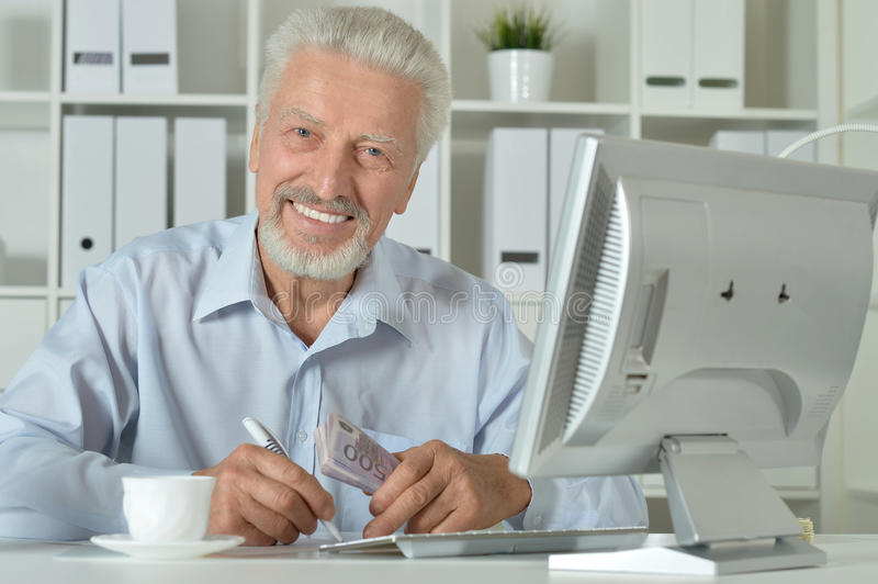 Senior man using computer. Portrait of a senior man using computer at office stock photography