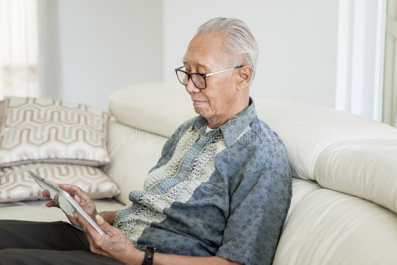 Senior man using a digital tablet computer royalty free stock photography