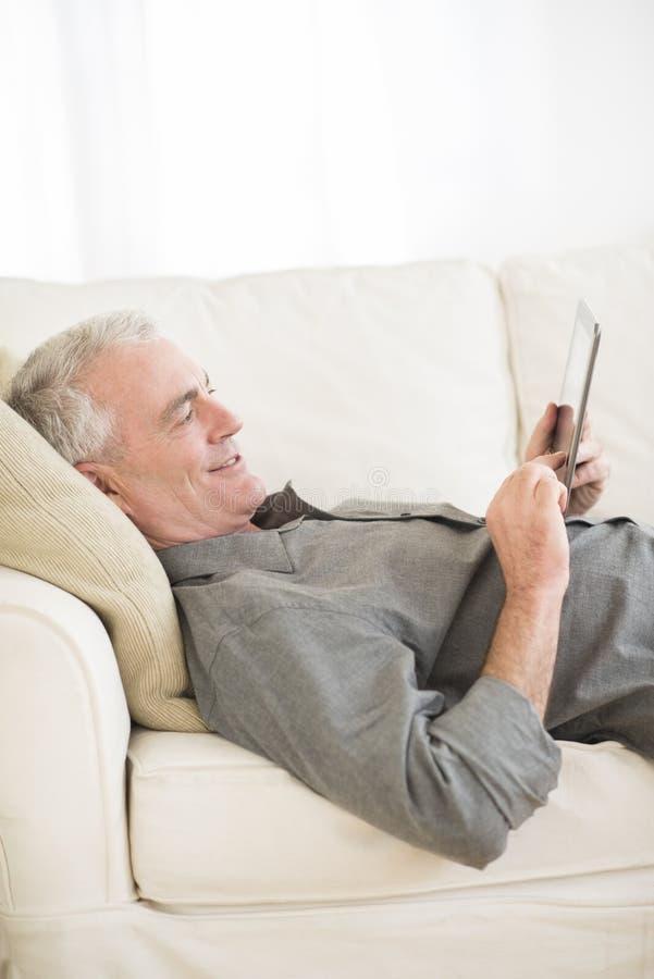 Download Senior Man Using Digital Tablet At Home Stock Photo - Image: 34512064