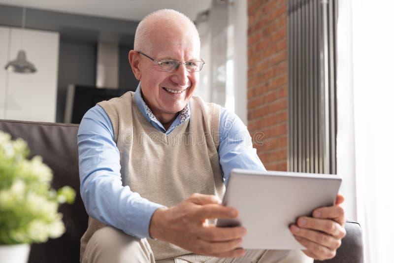 Senior man using digital tablet in living room royalty free stock image