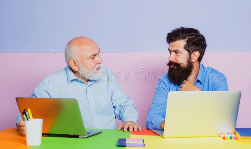 Senior man using a laptop computer with his son. Mature senior dad and young man sitting in office. Businessmen using royalty free stock photos