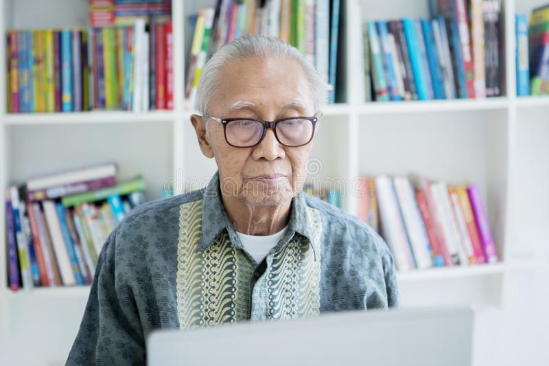 Senior man using a laptop computer in library stock photography