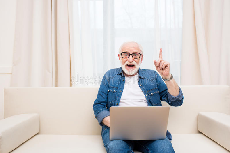 Senior man using laptop and pointing up with finger royalty free stock photo