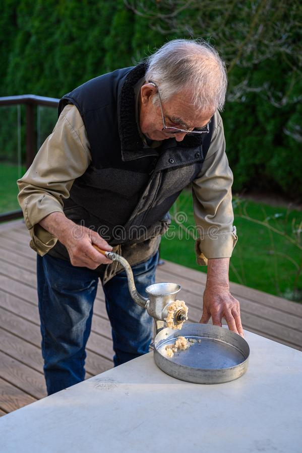 Senior man using manual grinder to grind up fresh razor clams for chowder, catch pan, and table stock images